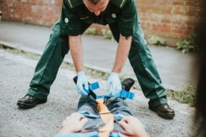 Point of view photo of an EMT assessing man on a gurney